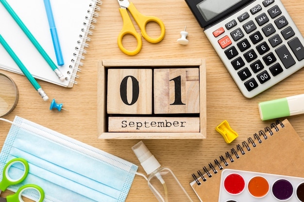 Bovenaanzicht van terug naar school essentials met kalender en medisch masker