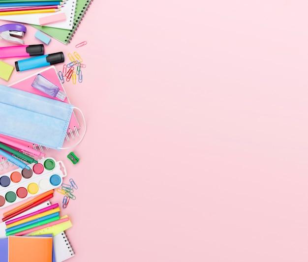 Bovenaanzicht van terug naar school essentials met medisch masker en aquarel