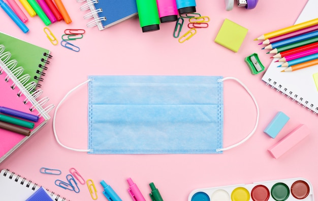 Bovenaanzicht van terug naar school essentials met medisch masker en notebooks