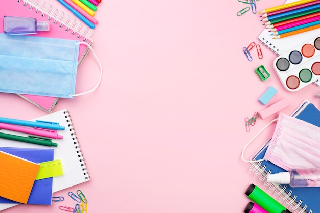 Bovenaanzicht van terug naar school essentials met medisch masker en potloden