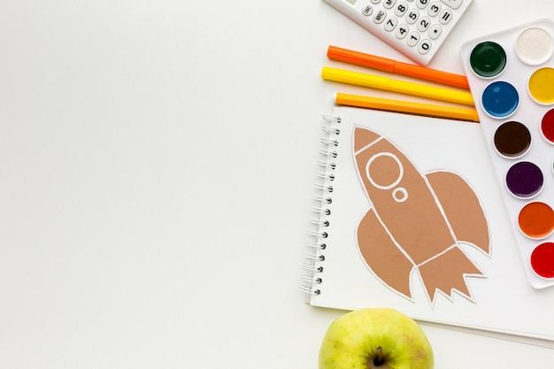 Bovenaanzicht van terug naar school essentials met notebook en aquarel