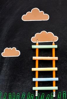 Bovenaanzicht van terug naar school ladder met potloden en wolken