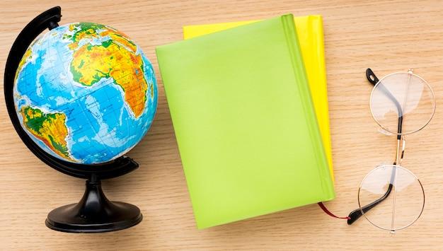 Bovenaanzicht van terug naar schoolbenodigdheden met bril en globe