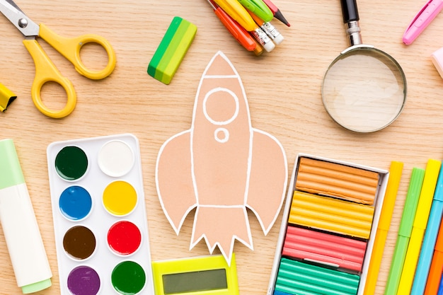 Bovenaanzicht van terug naar schoolbenodigdheden met kleurrijke potloden en aquarel
