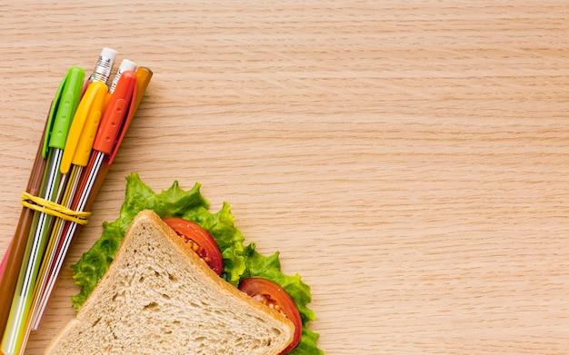 Bovenaanzicht van terug naar schoolbenodigdheden met sandwich en potloden