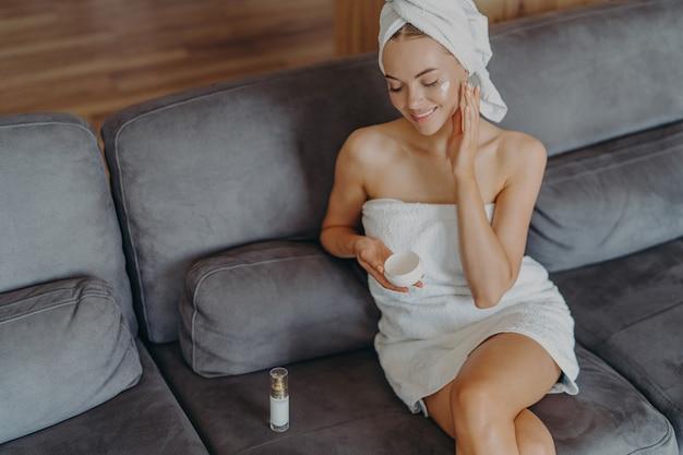 Bovenaanzicht van tevreden gezonde vrouw zit op comfortabele bank binnen