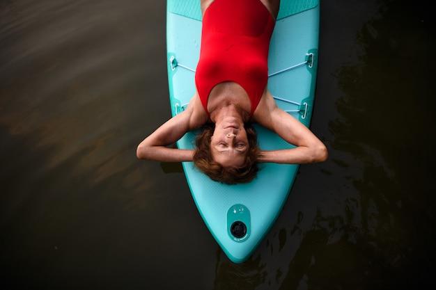 Bovenaanzicht van tevreden senior vrouw liggend op paddleboard op meer in de zomer, rusten.