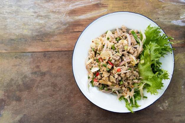 Bovenaanzicht van thais eten pittige varkensgehakt salade op houten tafel