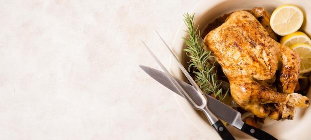 Bovenaanzicht van thanksgiving gebraden kip met bestek en kopie ruimte