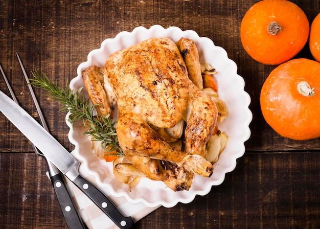 Bovenaanzicht van thanksgiving gebraden kip op plaat met bestek