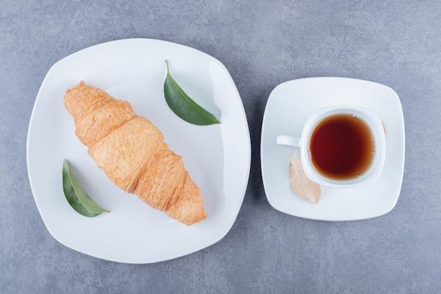 Bovenaanzicht van thee en croissants. klassiek ontbijt.