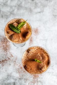 Bovenaanzicht van tiramisu dessert met munt in een glas op grijs
