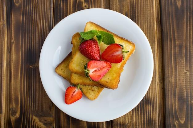 Bovenaanzicht van toast met aardbeien in de witte plaat