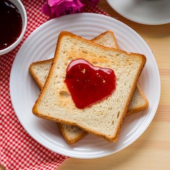 Bovenaanzicht van toast met jam en roos