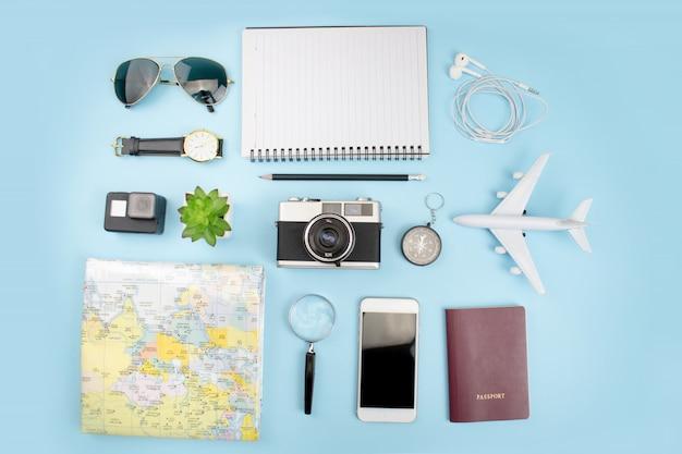 Bovenaanzicht van toeristische accessoires met filmcamera's, kaarten, paspoorten, horloges, kompassen