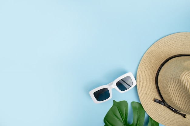 Bovenaanzicht van toeristische accessoires met hoeden, zonnebrillen en zomerbladeren op een blauwe achtergrond. met kopie ruimte