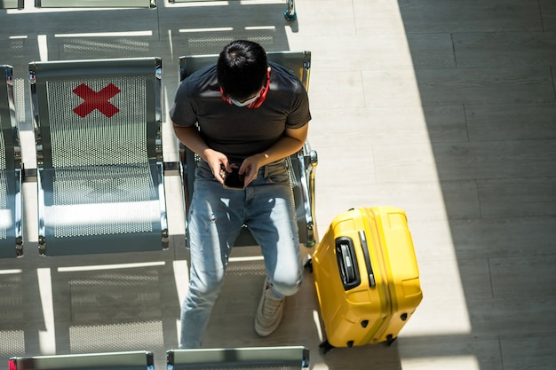 Bovenaanzicht van toeristische jongeman met gezichtsmasker bescherming zitten op zithoek in de buurt van bagage en het gebruik van telefoon in luchthaventerminal.