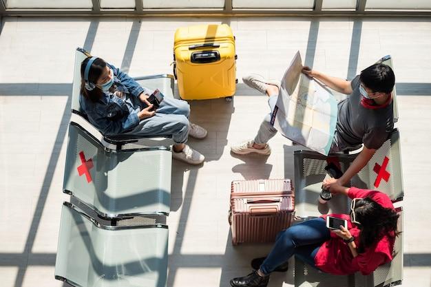 Bovenaanzicht van toeristische jongeren met gezichtsmasker zitten op zithoek in de buurt van bagage om te wachten op vertrek in luchthaventerminal. nieuwe normale reislevensstijl om covid19 te voorkomen.