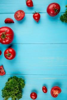 Bovenaanzicht van tomaten en koriander op blauw oppervlak met kopie ruimte