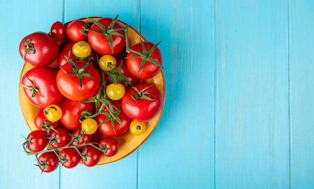 Bovenaanzicht van tomaten in kom aan de linkerkant en blauwe oppervlak met kopie ruimte