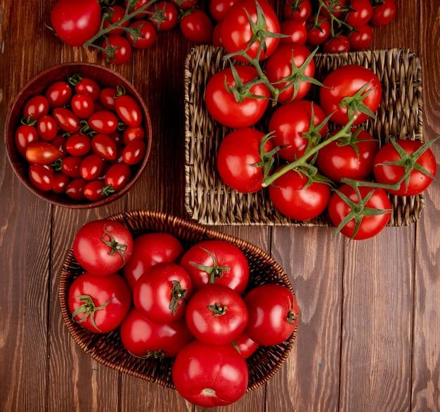 Bovenaanzicht van tomaten in kom mand en plaat op houten oppervlak