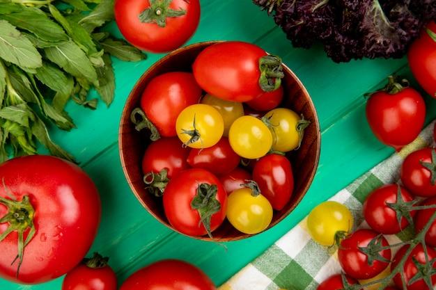Bovenaanzicht van tomaten in kom met groene muntblaadjes en basilicum op groene ondergrond
