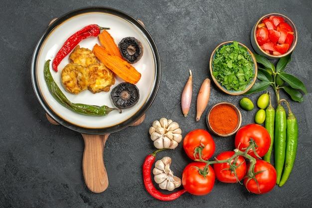 Bovenaanzicht van tomaten kleurrijke groenten kruiden kruiden de smakelijke schotel op het bord
