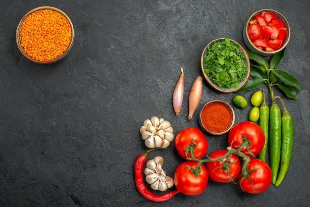 Bovenaanzicht van tomaten, knoflook, ui, hete pepers, tomaten, kruiden, kruiden, kom van linze