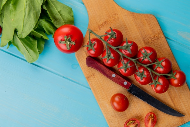 Bovenaanzicht van tomaten met mes op snijplank en spinazie op blauwe ondergrond