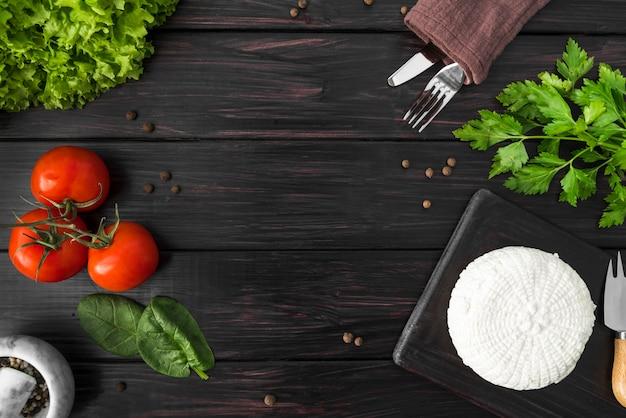 Bovenaanzicht van tomaten met spinazie en bestek