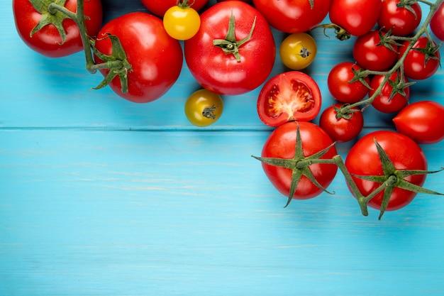 Bovenaanzicht van tomaten op blauwe oppervlak met kopie ruimte