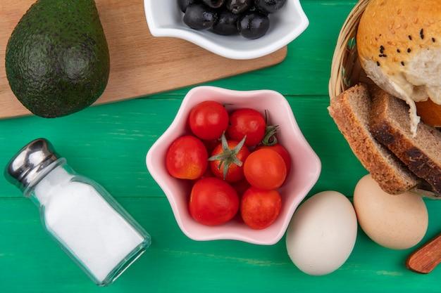 Bovenaanzicht van tomaten op een roze kom met avocado en zwarte olijven op een houten keuken bord met een emmer brood op groen oppervlak