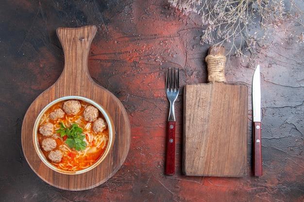 Bovenaanzicht van tomatengehaktballetjessoep met noedels in een bruine kom en snijplank met vork en mes op donkere achtergrond