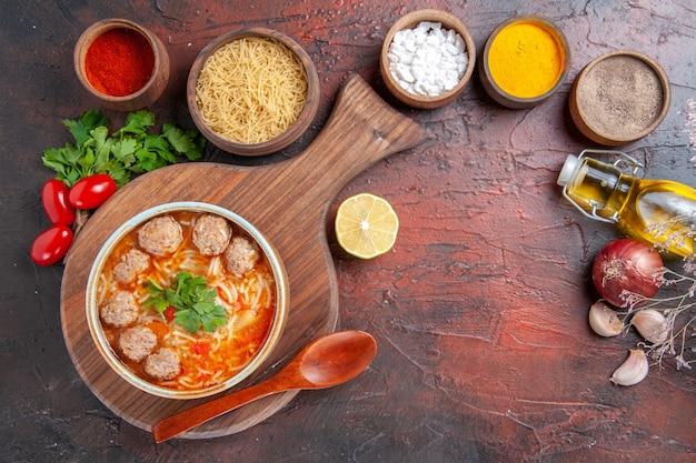 Bovenaanzicht van tomatengehaktballetjessoep met noedels in een bruine kom en verschillende kruidenoliefles-ui-knoflook op donkere achtergrond