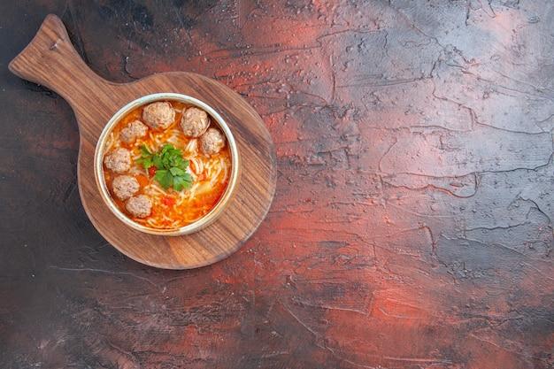 Bovenaanzicht van tomatengehaktballetjessoep met noedels in een bruine kom op donkere achtergrond