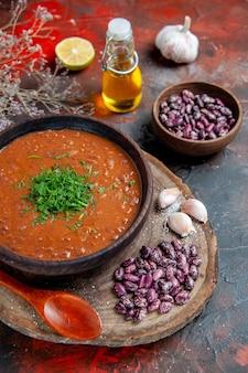 Bovenaanzicht van tomatensoep bonen knoflook op houten snijplank en olie fles op mix kleurentafel