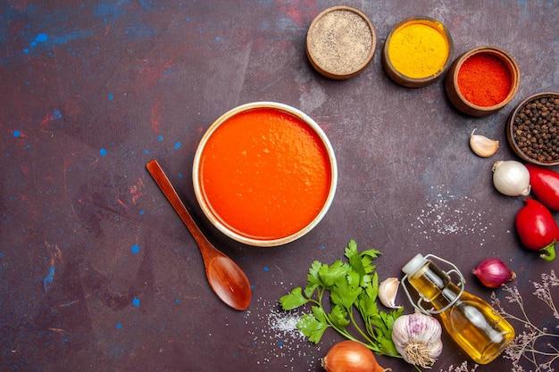 Bovenaanzicht van tomatensoep gekookt van verse tomaten met kruiden op zwart