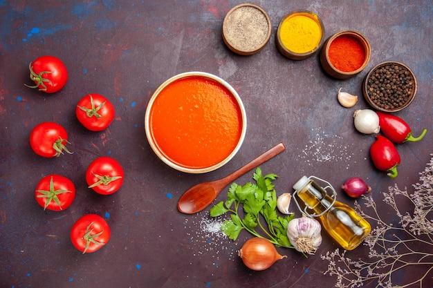 Bovenaanzicht van tomatensoep gekookt van verse tomaten met kruiden op zwarte tafel