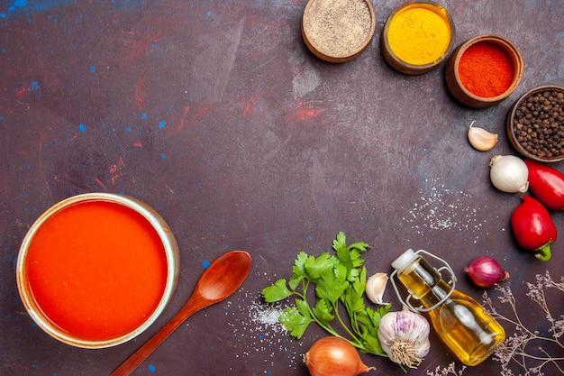 Bovenaanzicht van tomatensoep gekookt van verse tomaten met verschillende smaakmakers op zwart