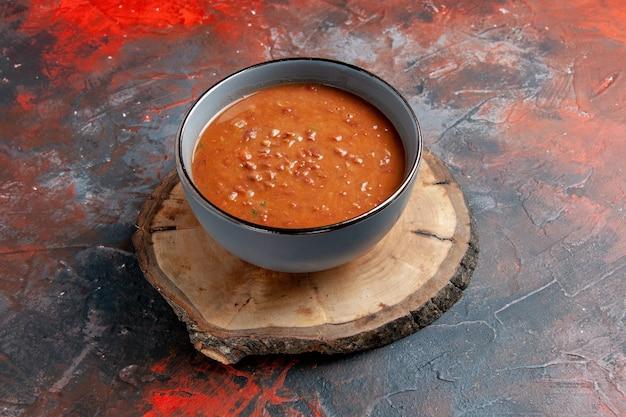 Bovenaanzicht van tomatensoep in een blauwe kom op een bruin houten dienblad op gemengde kleurentafel