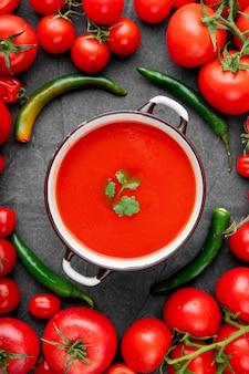 Bovenaanzicht van tomatensoep in een pan gegarneerd met peterselie en groene chili pepers en tomaten op zwarte achtergrond