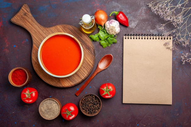Bovenaanzicht van tomatensoep met kruiden op zwart