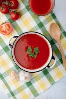 Bovenaanzicht van tomatensoep met lepel en groenten rond op geruite doek oppervlak