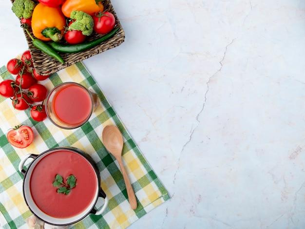 Bovenaanzicht van tomatensoep met tomatensap en lepel en groenten aan de linkerkant op witte ondergrond