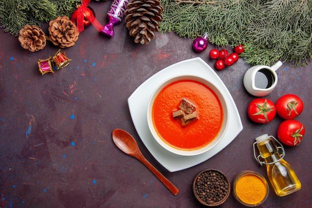 Bovenaanzicht van tomatensoep met verse tomaten en kruiden op zwart