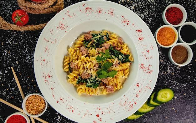 Bovenaanzicht van tonijnfusilli met spinazie en parmezaanse kaas