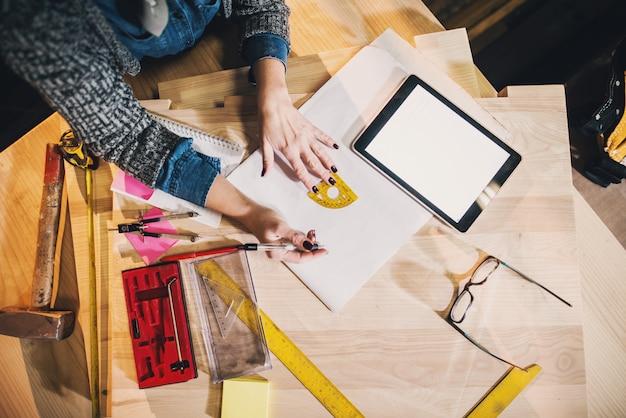 Bovenaanzicht van tools en papieren en tablet op workshop. vrouw bedrijfs bovenaanzicht concept