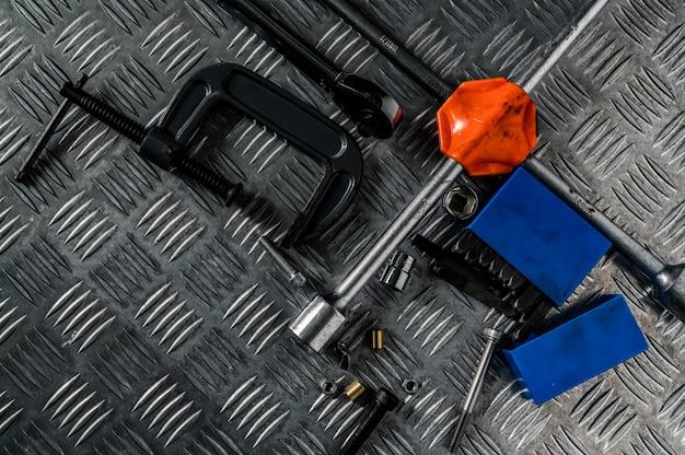 Bovenaanzicht van tools op industriële metalen checker plaat. metalen schijf voor antislip. moer, bouten en inbussleutel op metalen plaatvloer. zilveren bult grond.