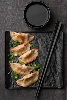 Bovenaanzicht van traditionele aziatische dumplings op leisteen met stokjes