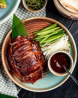 Bovenaanzicht van traditionele aziatische gerechten pekingeend met komkommers en saus op een bord